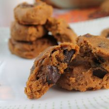 horizontal image from eye level of a white plate stacked with soft pumpkin cookies loaded with chocolate chips