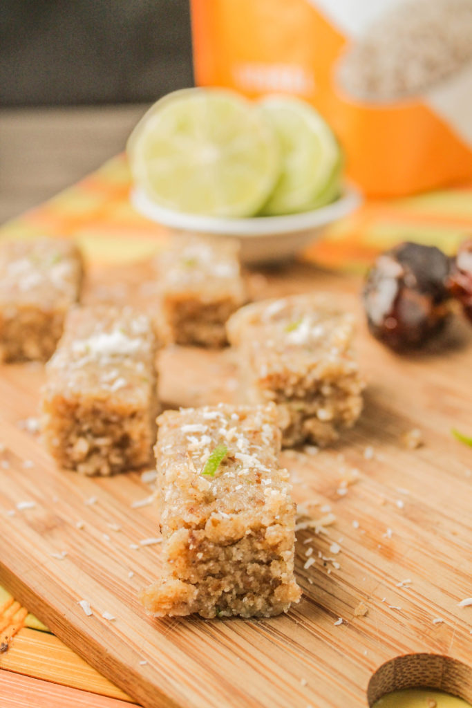 rectangle squares of nut, coconut, date, hemp, and lime bars atop a bamboo cutting board