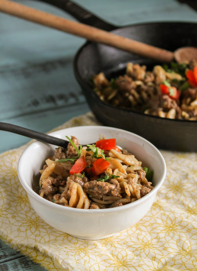 vertical image of healthy beef noodle one skillet meal in a white bowl with a cast iron pan in the background