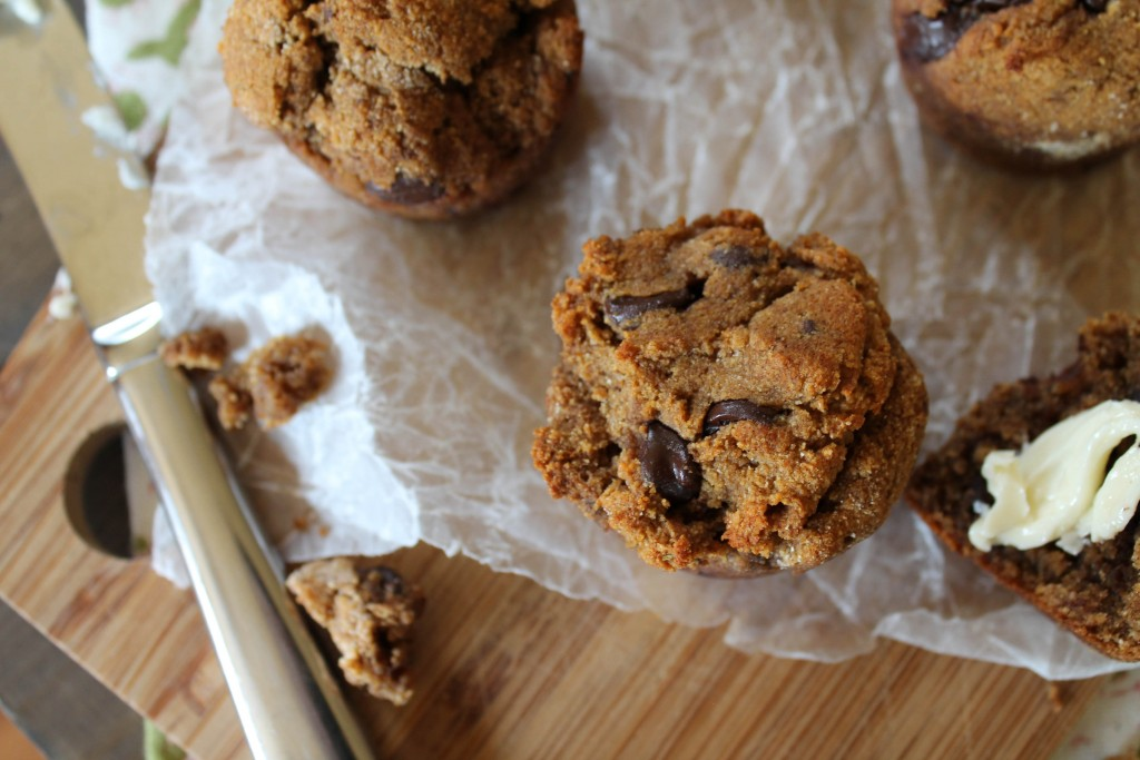 overhead view of several chocolate chip style muffins atop a bamboo cutting board and crumpled parchment paper