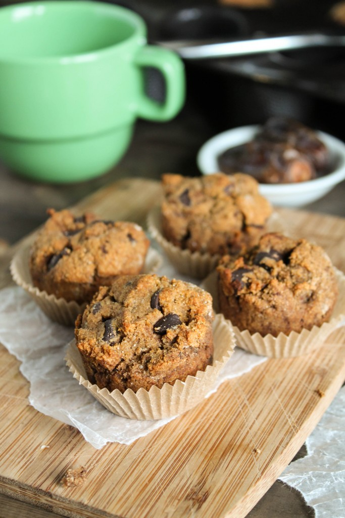 4 mini sweet potato muffins with chocolate chips atop a bamboo cutting board with green coffee mug