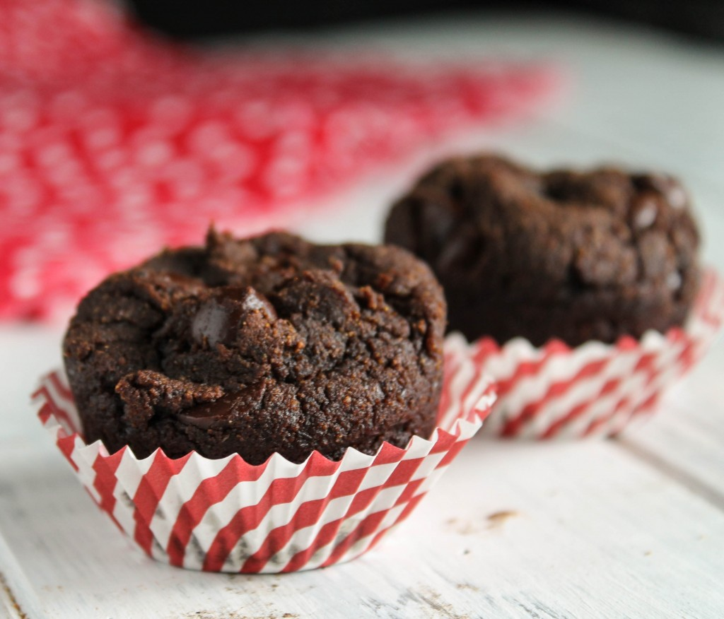 two chocolate chip studded mini muffins in red and white paper liners on a white wooden board