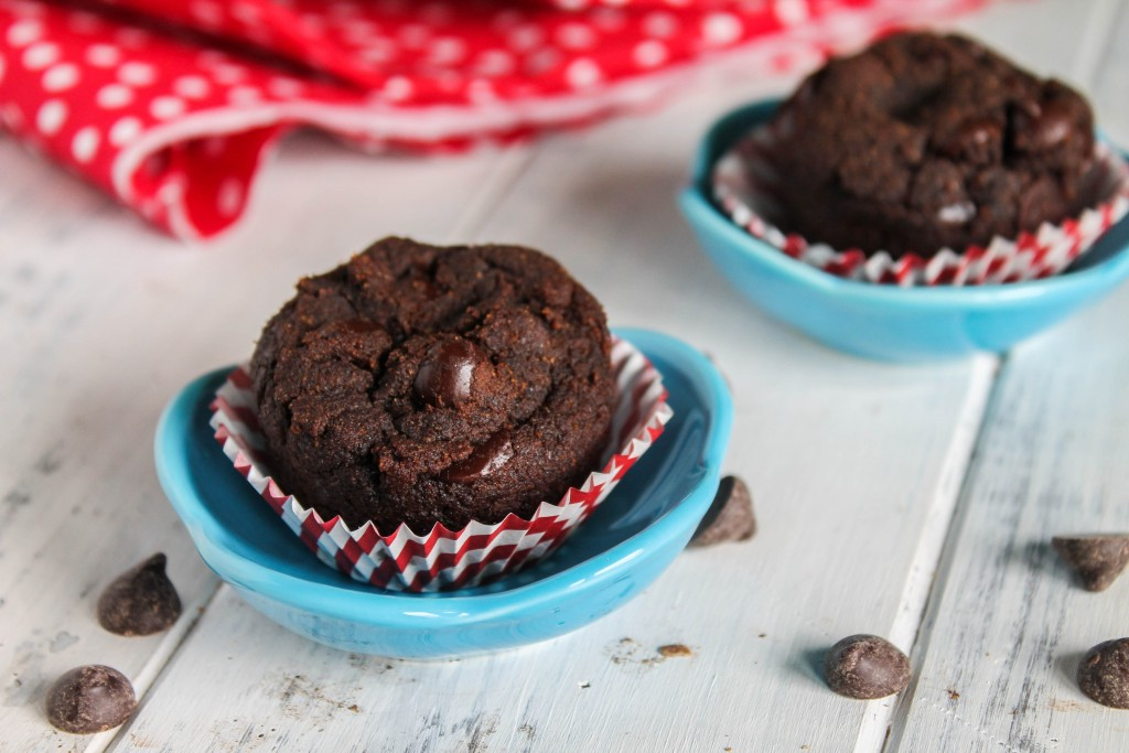 horizontal image of two chocolate mini muffins pebbled with chocolate chips in red and white barber striped paper muffin liners and turquoise dipping dish