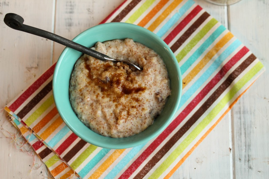 overhead shot of a turquoise bowl filled with cinnamon topped gluten free porridge on a brightly striped cloth