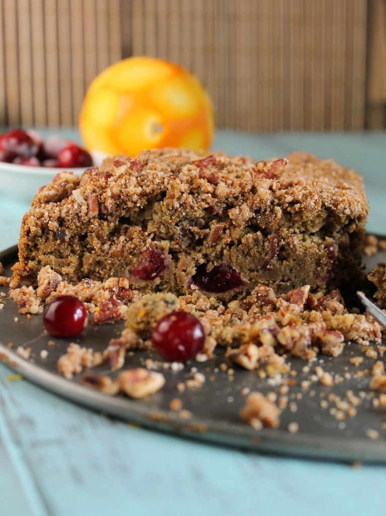 close up of a slice of cranberry studded coffee cake with a crumb topping