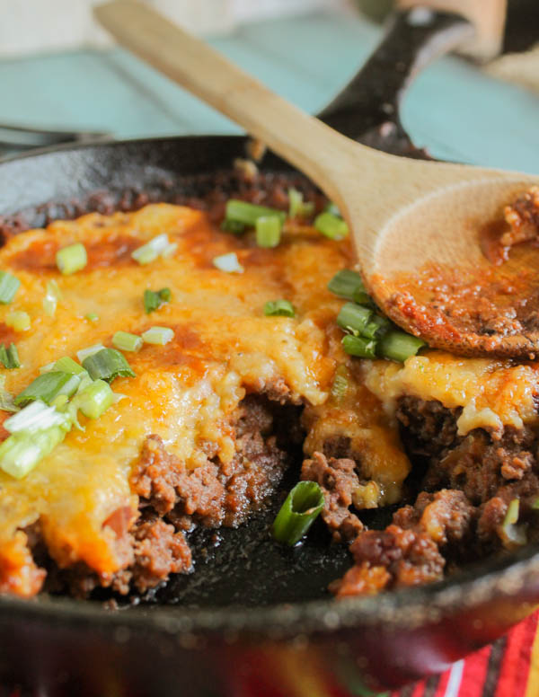 vertical image of a spooned up serving on tender ground beef with a chewy tamale topping and a garnish of green onions and a wooden spoon