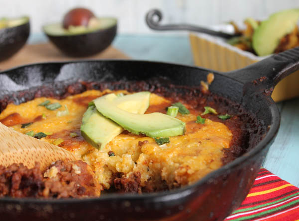 a cast iron skillet filled with ground beef, pinto beans, and topped with a corn masa topping with  cheese and avocado