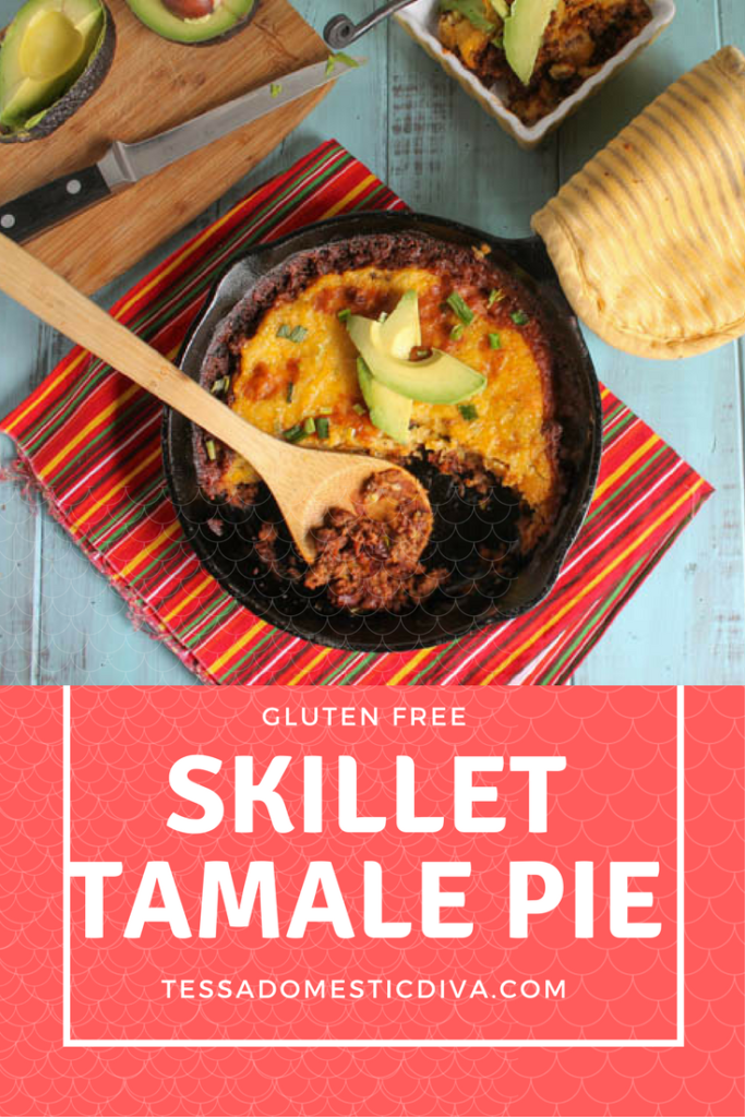optimized for pinterest gluten free tamale pie from overhead in a cast iron skillet with a garnish of fresh sliced avocado on turquoise wood board