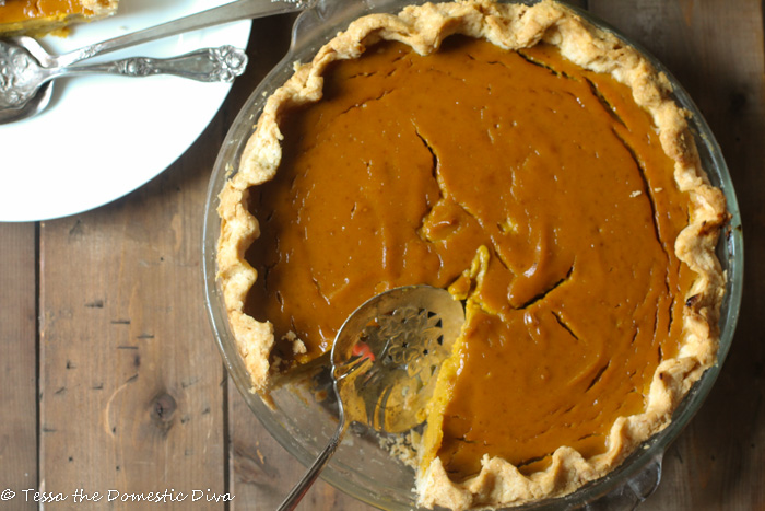 birds eye view of a pumpkin pie with a slice removed with a waved crust on a dark wooden surface