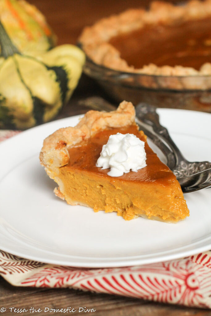 a slice of pumpkin pie with a dollop of whipped cream on a white plate with fall squash and a full pie in the background