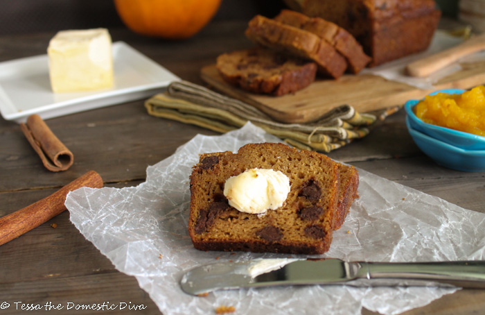 eye level shot of a sliced pumpkin bread with a dollop of fresh butter and a fresh orange pie pumpkin in the background