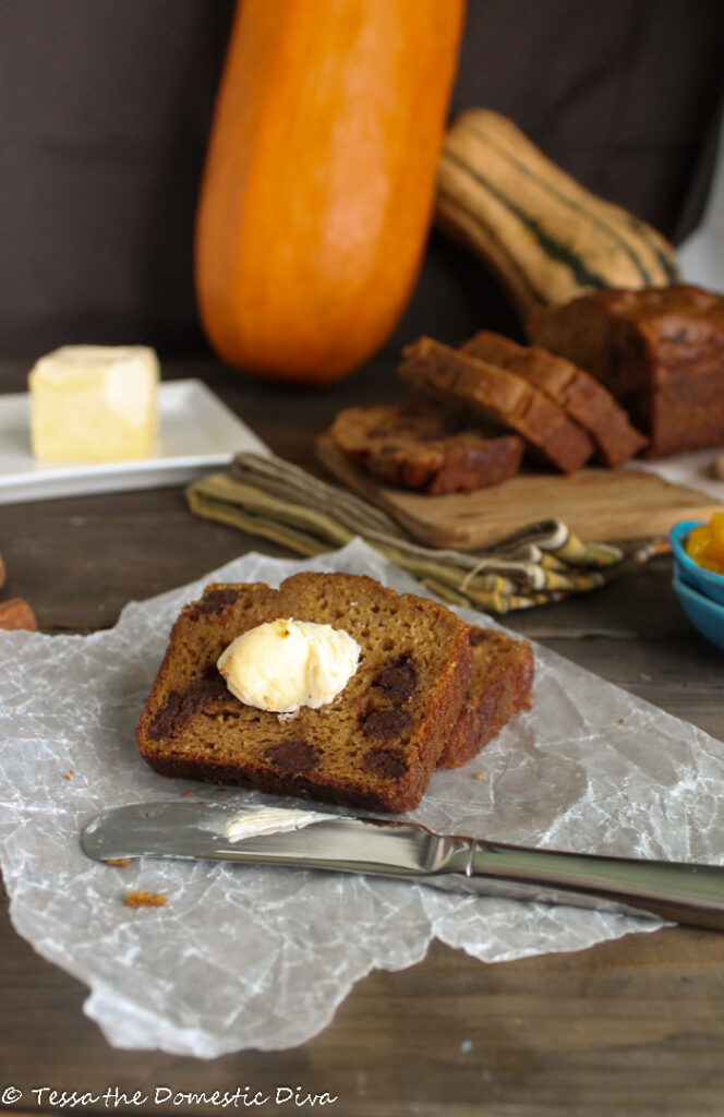 sliced pumpkin bread with a slather of butter o a parcemnt paper and dark wood surface with fresh pumpkin