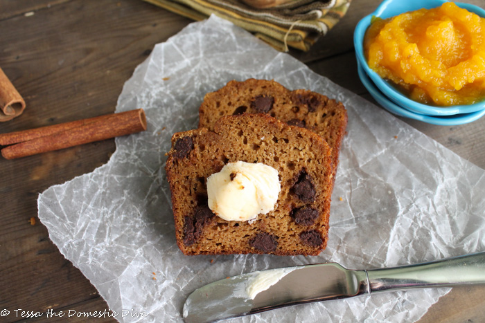 birdseye view of two slices of grain free pumpkin bread with chocolate chips atop a piece of white parchment paper and small bowl of fresh pumpkkin puree and cinnamon stick