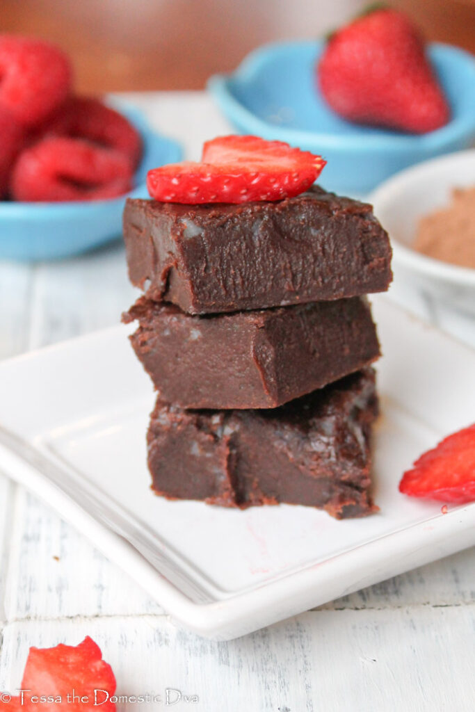 a stack of three egg free gluten free chocolate brownies on a white plate with fresh sliced strawberries