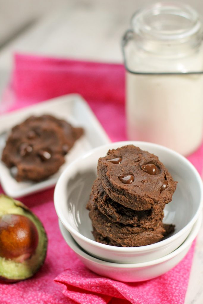 dense and fudgy stack of chocolate cookies studded with molten chocolate chips and halved avocado half on the left