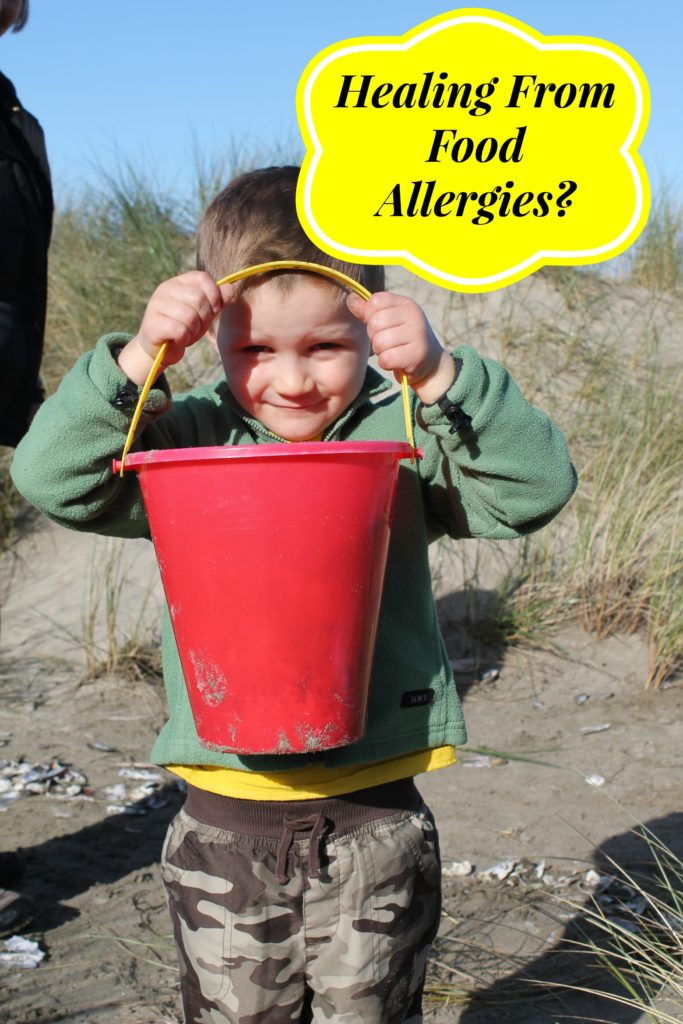 a 3 year old boy on a sunny beach with a red plastic bucket help up to his face