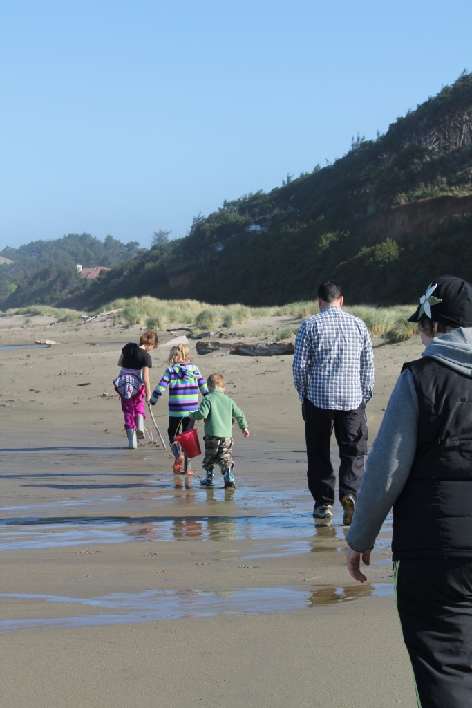 family with three kids walking in a line down a beach
