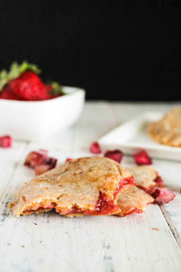 strawberry rhubarb hand pies on a white washed board with diced fresh rhubarb and whole strawberries