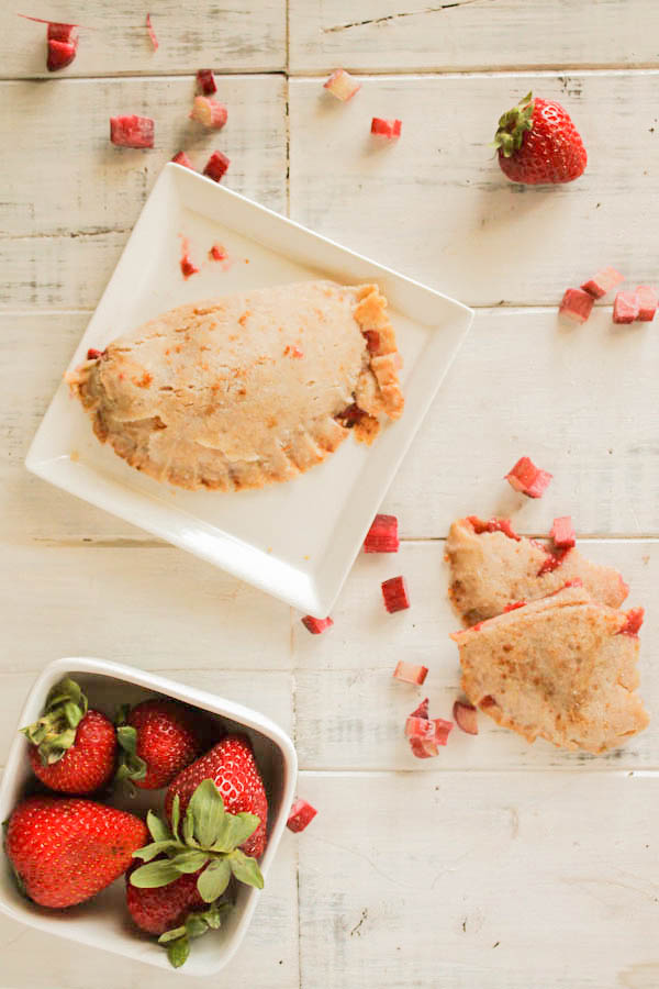 a white wooden board with a square white plate topped with an empanada with strawberry and rhubarb