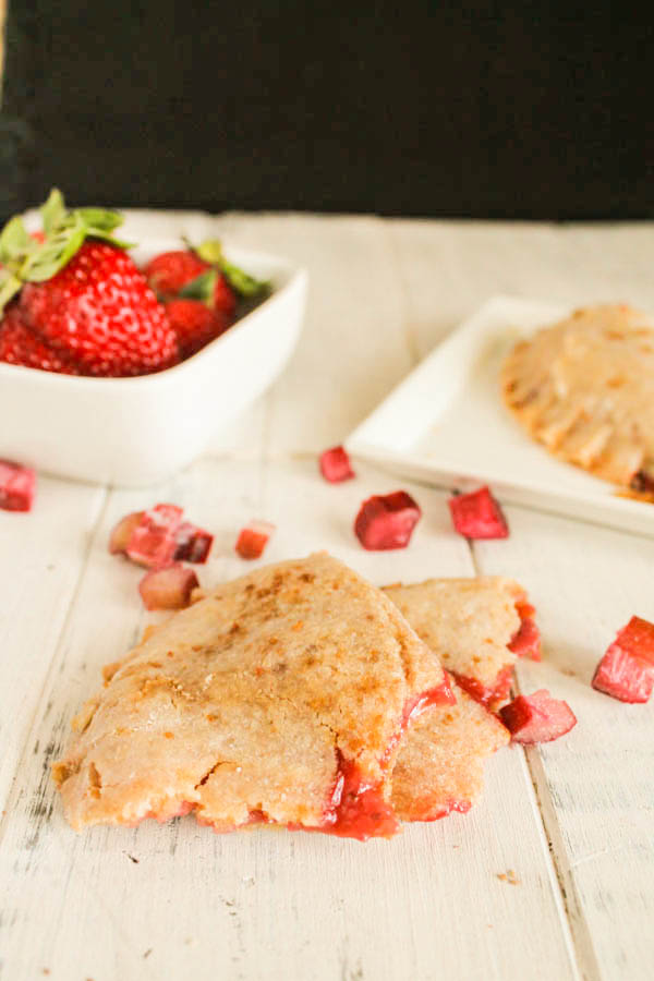 a white washed board with a tron cassava flour starwberry rhubarb pie and fresh berries