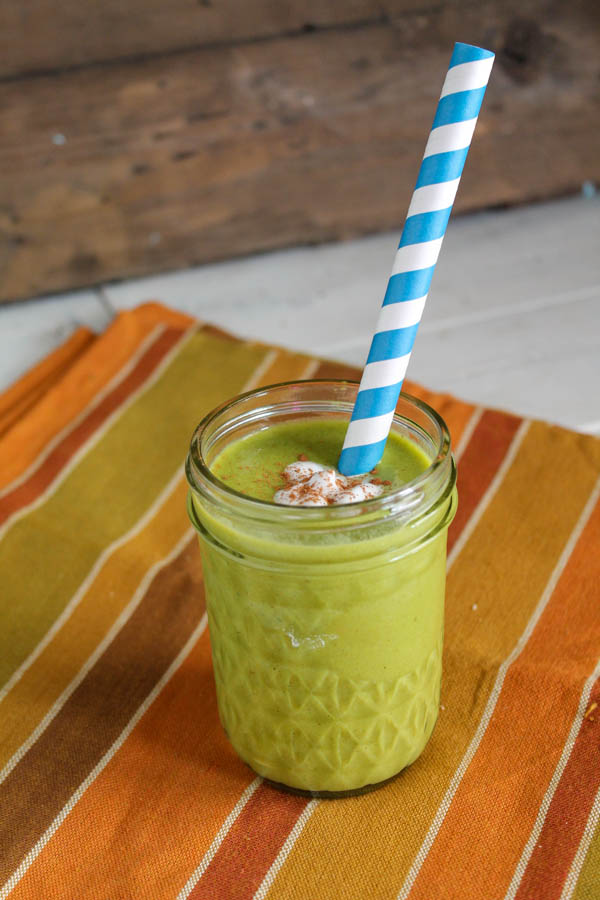 vertical image of a green pumpkin smoothie with a paper straw on a autumn striped cloth