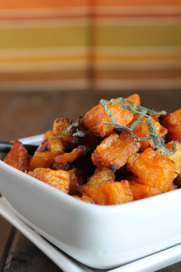 caramelized roasted butternut squash cubes topped with a ribbon of fresh sage in a square white bowl