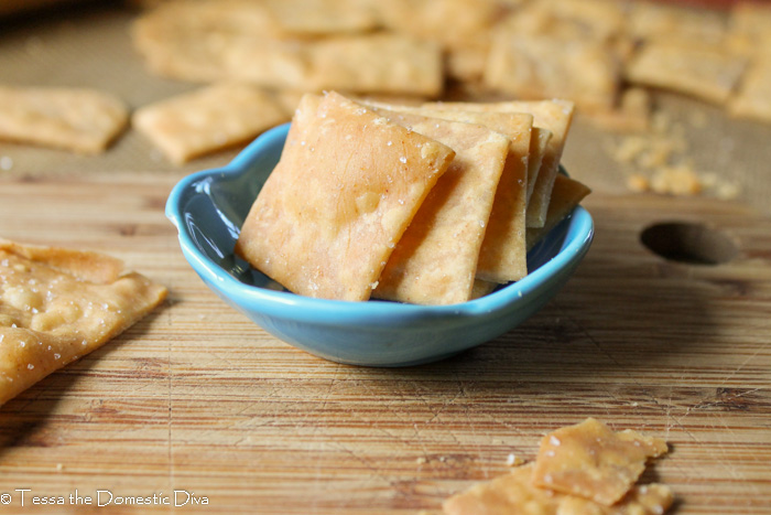 a small blue bowl filled with crispy golden square homemade crackers on a bamboo cutting board