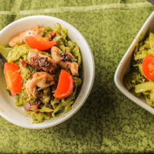 overhead shot of two white bowls filled with green pesto spaghetti squash noodles topped with crispy bacon, chicken thighs, and sliced cherry tomatoes