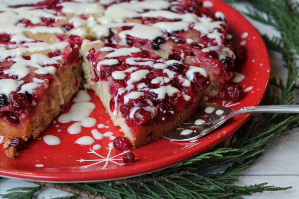 sliced cranberry upside down coffee cake on a red snowflake plate with a silver serving spatula