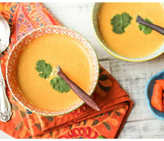 two bowls of orange carrot soup on an orange paisley cloth from overhead