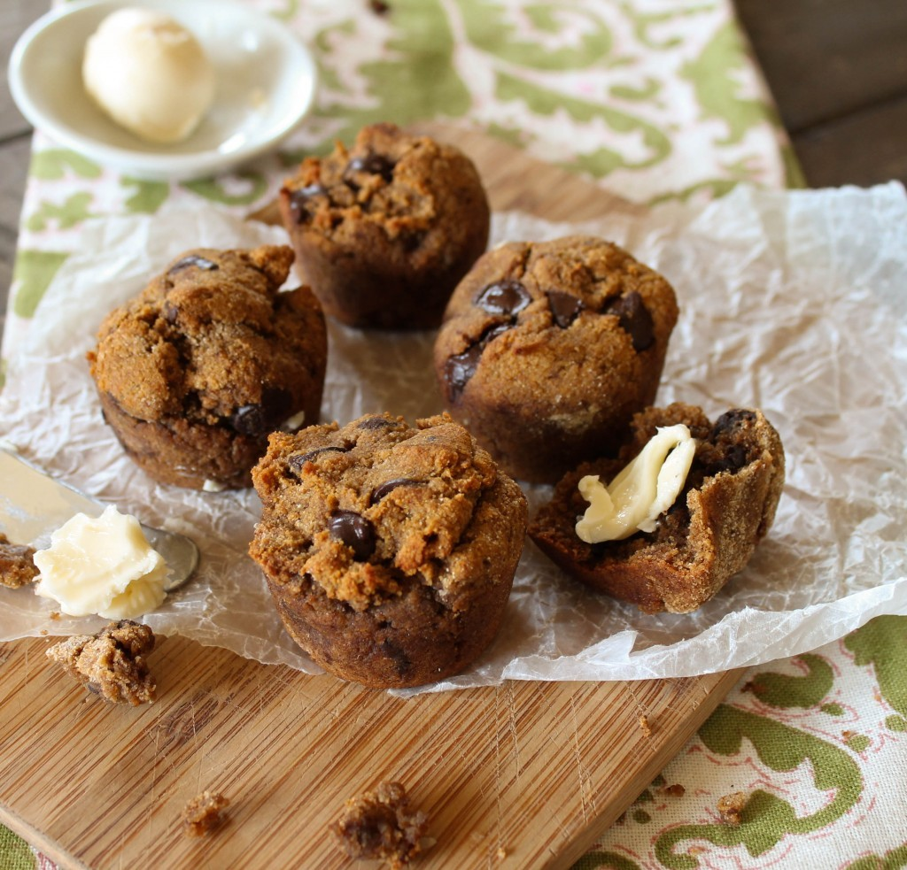 mini sweet potato muffins with a pat butter arranged on a wooden board with a paleo green linen