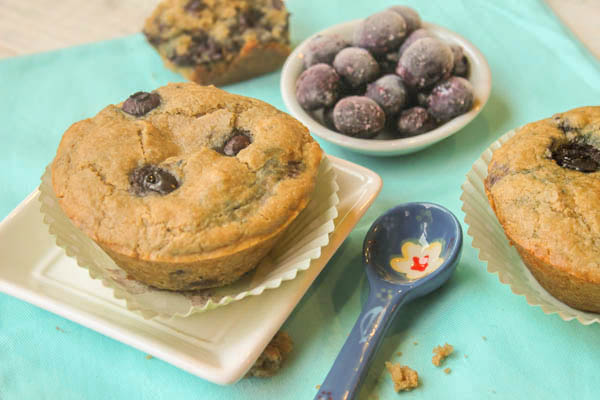 paleo blueberry muffins on a white square plate in a natural paper baking cup. and a hand painted blue teaspoon