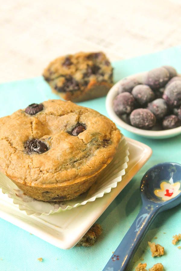 a blueberry studded muffin atop a white plate in a mint green paper baking linee with fresh blueberries in the background