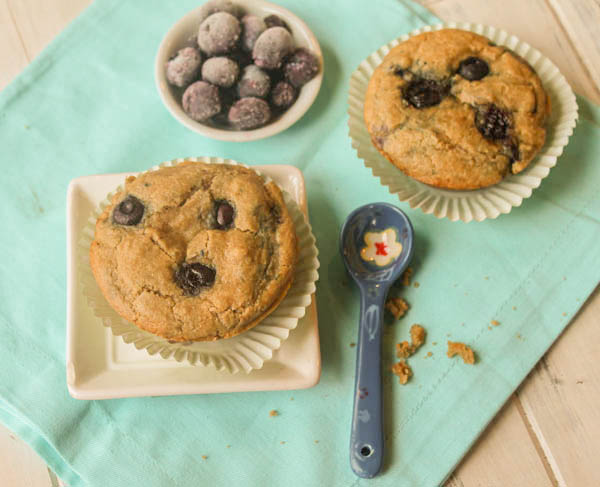 overhead shot of blueberry muffins on a turquoise linen baked in mint green paper liners with a bowl of fresh blueberries
