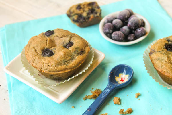 blueberry muffins with large fresh blueberries on a blue napkin with frozen blueberries in background