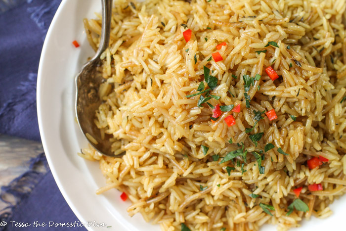 a white filled with rice pilaf and a silver spoon digging in