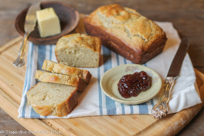 two golden hued min loaves of almond bread with a stick of butter