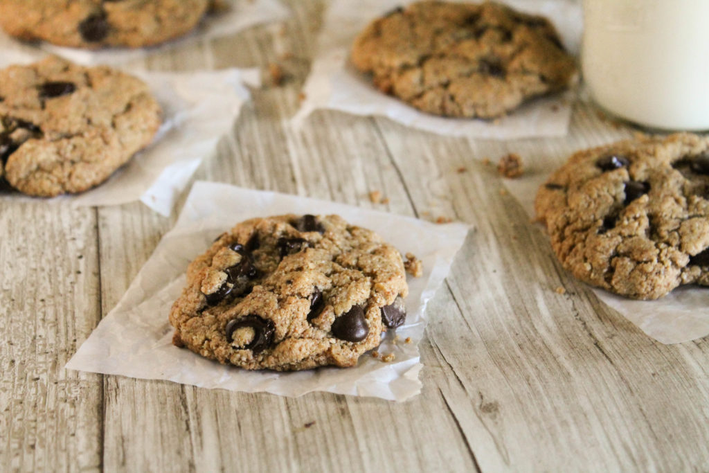 horizontal image of flourless paleo chococlate chip cookies arranged on a wooden surface on individual squares of parchment paper and a glass of milk