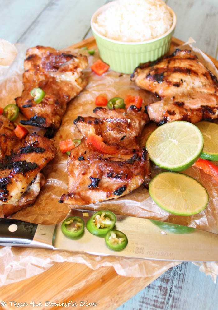 a large chef knife with grilled chicken thighs with rice, lime, red pepper, and green chili