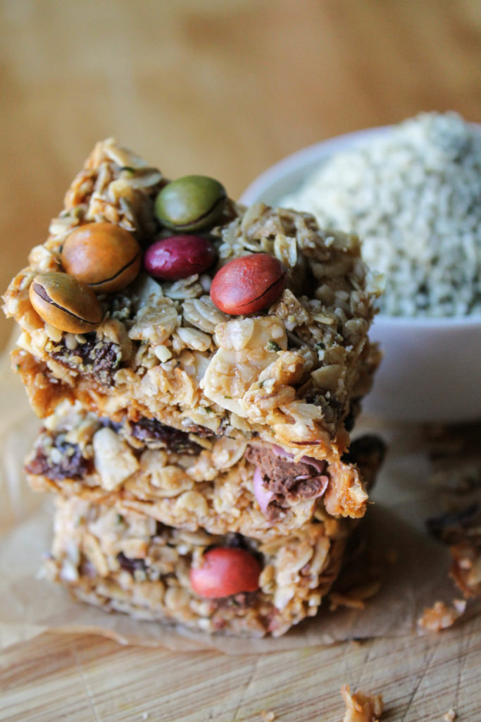 three square homemade healthy granola bars stacked on a bamboo cutting board.