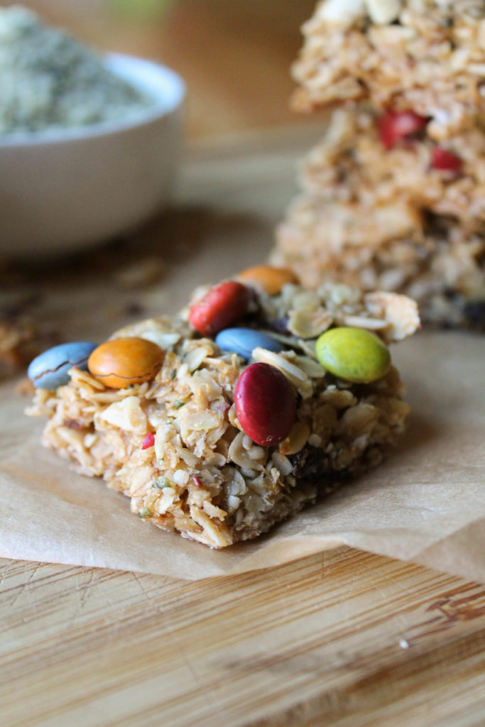 homemade granola bars with/ natural dye m & m's on a wooden board.