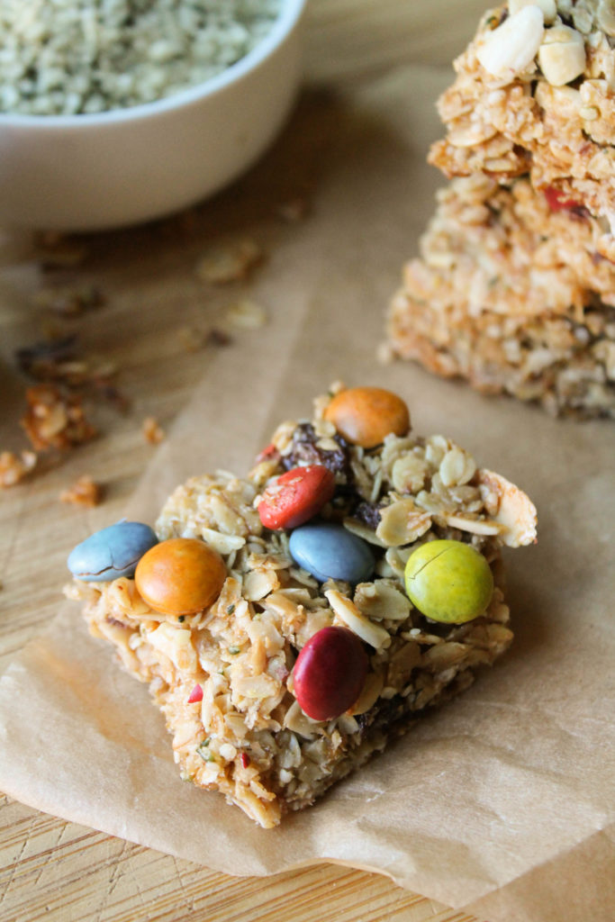 a hemp granola bar with dye free m & m's on parchment and a wooden cutting board.