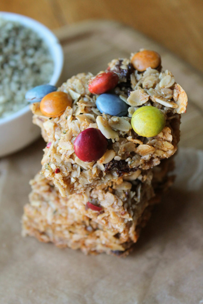 a stack of three homemade granola bars with natural dye chocolate candies.
