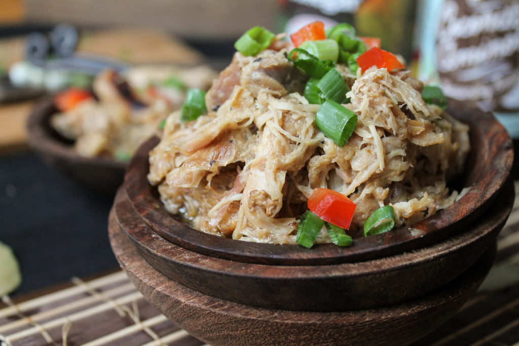 horizontal image of shredded Filipino chicken in three stacked dark wooden bowls with a sliced green onions and diced red bell pepper