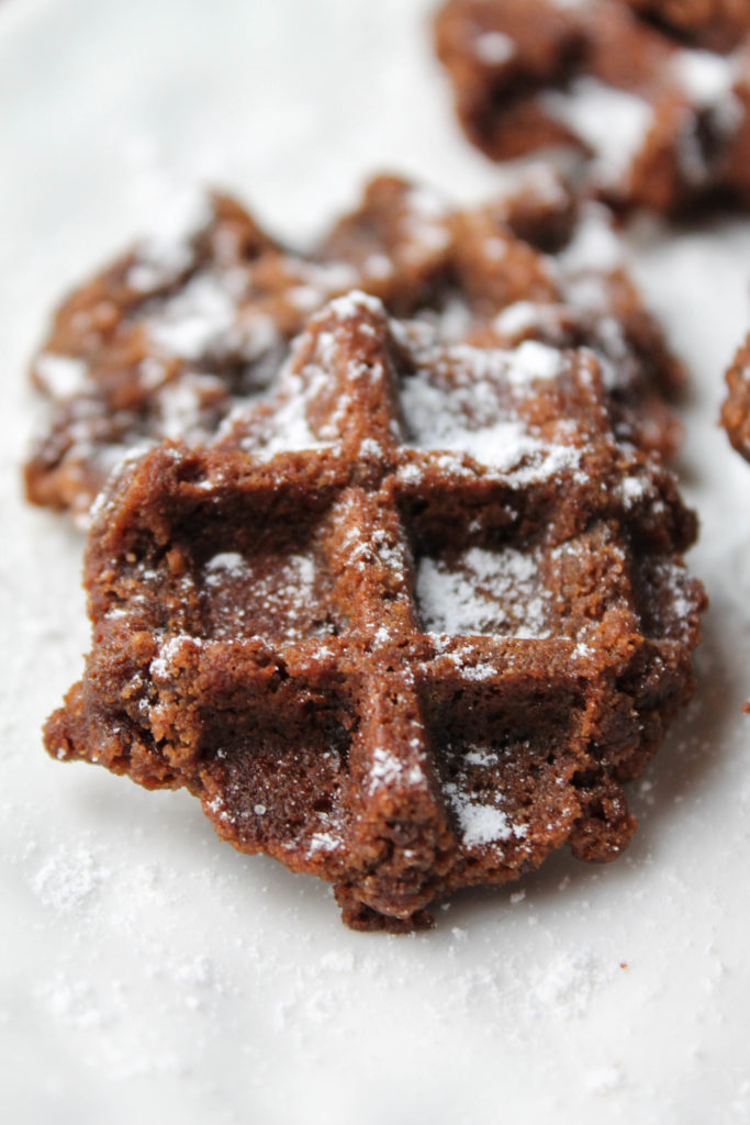 gluten free chocolate cookies baked in a waffle iron and dusted with powdered sugar