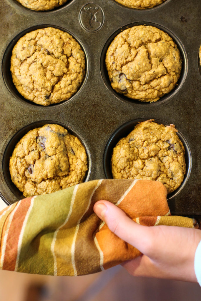 pumpkin oat muffins in a dark muffin tine from overhead studded with chocolate chips