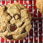 paleo chocolate chip cookie with chewy texture on a metal cooling rack and red with white polka dot background