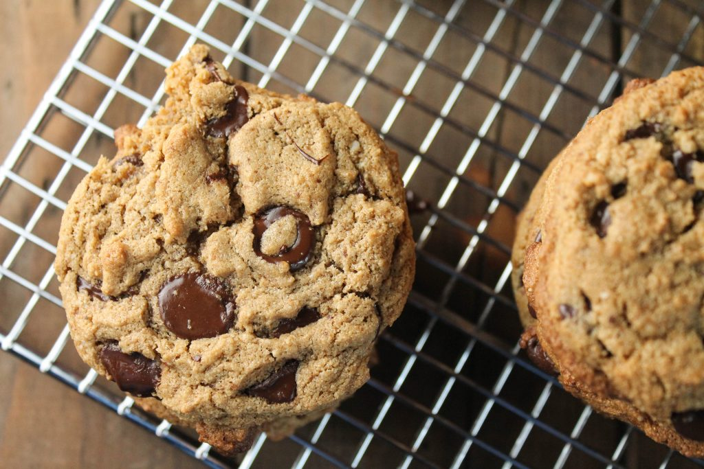 overhead view of a chocolate chip studded cookie atop a stainless steel cooling rack