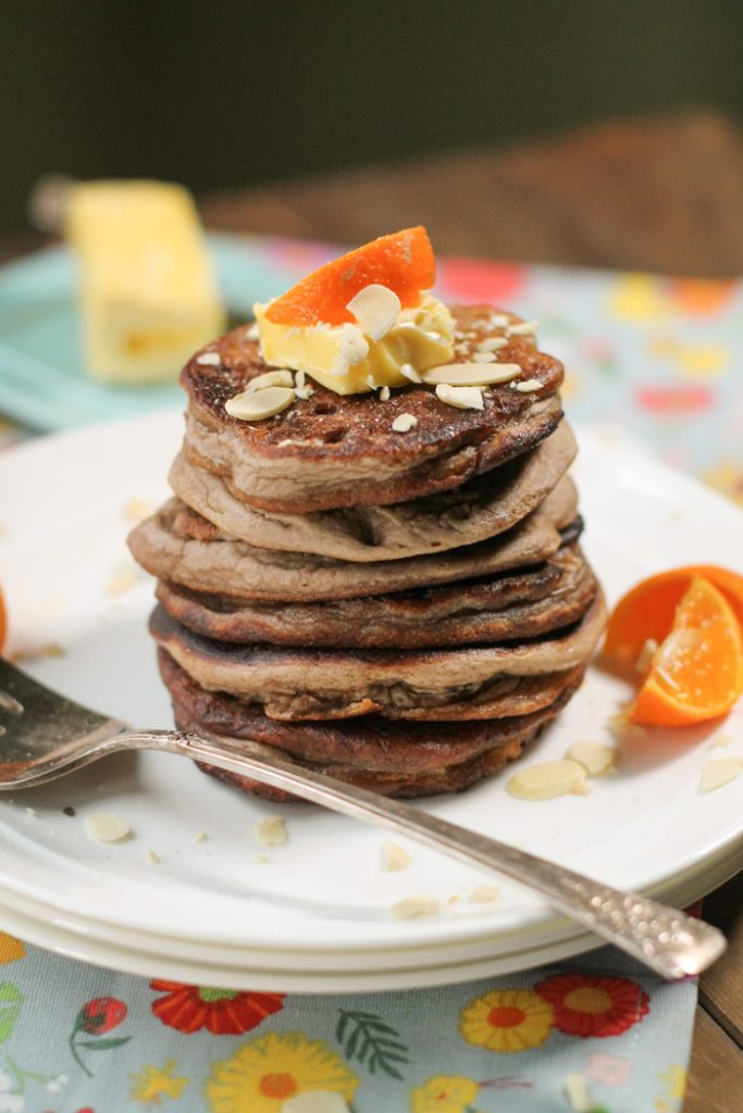 a large stack of brown teff pancakes with fresh oranges and sliced almonds on a white plate