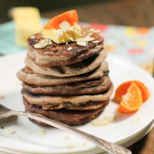 horizontal image of a stack of 6 wholegrain pancakes topped with a pat of butter, sliced almonds, and orange wedges on a white plate atop a dark wood surface